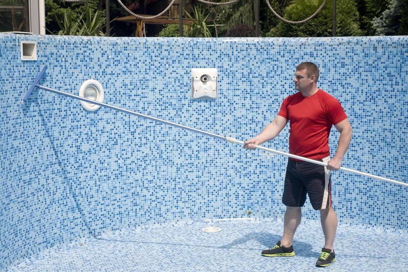 man brushing out the pool tiles